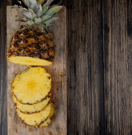 top-view-cut-sliced-pineapple-cutting-board-left-side-wooden-background-with-copy-space_141793-8250
