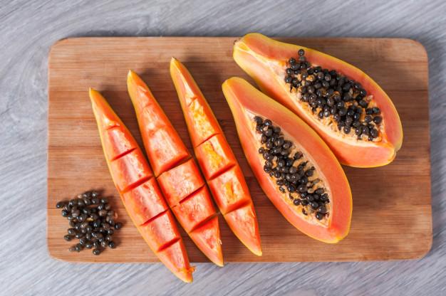 papaya-fruit-cut-slices-wooden-background_114541-219
