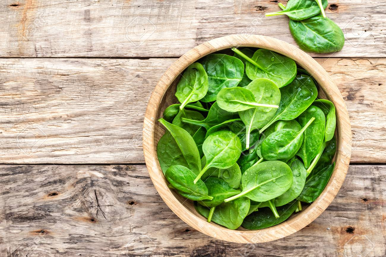 Fresh baby spinach leaves in bowl on wooden background